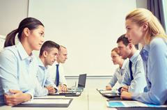 smiling business people having conflict in office - stock photo