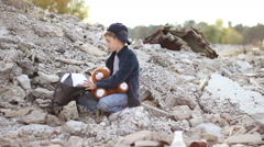 Homeless orphan boy with a soft toy in his hands looking for food in the package Stock Footage