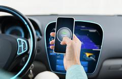 Hands with start engine icon on smartphone in car Kuvituskuvat