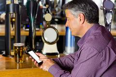 Man with grey hair using mobile phone Stock Photos