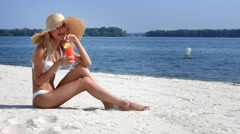 Girl sitting on beach near the river and drink cocktail Stock Footage