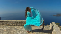 Beautiful happy smiling Girl spinning in blowing blue dress over sea. Stock Footage