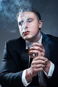 Smoker in suit with cigarette and glass of whiskey Stock Photos