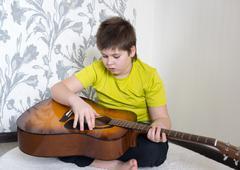 Teenage Boy plays an acoustic guitar Stock Photos