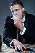 Portrait of handsome young mobster with smoking cigarette and gu Stock Photos