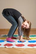 Little girl playing twister - stock photo