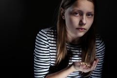 Drug addicted teenager girl with pills Stock Photos