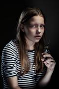 Drug addicted teenager girl with syringe, dark portrait - stock photo