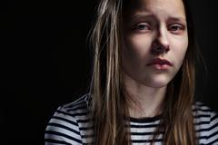Dark portrait of a crying teen girl Stock Photos