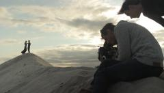 Stock Video Footage of The cameraman shoots the scene with a romantic couple on a sandy desert mountain