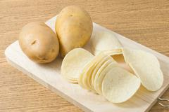 Snack Food, Potato Tuber with Potato Chips or Crisp on Cutting Board. - stock photo