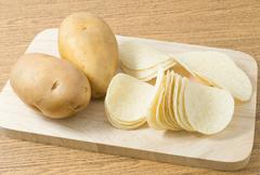 Snack Food, Potato Tuber with Potato Chips or Crisp on Wooden Board. - stock photo