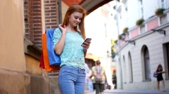 Girl with colorful shopping bags writing message to her friend using smarphone. Stock Footage