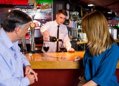 Bartender offering glasses of wine to couple Stock Photos