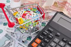 Russian ruble banknotes and shopping cart with question marks - stock photo