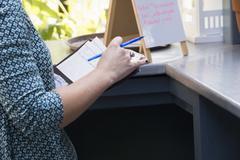 A person in a cafe holding a bill and a pen standing by a bar counter a menu Stock Photos