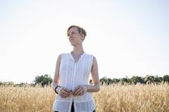 Half length portrait of a young woman standing in a cornfield. Stock Photos