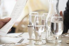 Close up of wine and water glasses and place settings at a table in a - stock photo