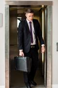 Handsomne businessman with portfolio leaving elevator Kuvituskuvat