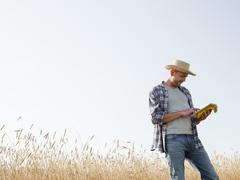 A man in working clothes jeans and straw hat using a digital tablet standing in Stock Photos