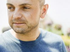 Head and shoulders portrait of a man with stubble in a blue teesirt. - stock photo