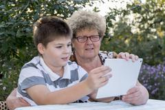 Granny with grandson watching tablet in nature Stock Photos