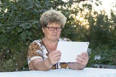 Granny with grandson watching tablet in nature - stock photo