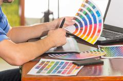 Male hands holding up pantone palette, colormap spread out in front of laptop on - stock photo
