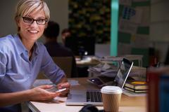Female Office Worker With Coffee At Desk Working Late Stock Photos