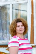 Woman at the window of  country house Stock Photos