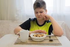 Teenager boy refuses to eat oatmeal for breakfast Stock Photos