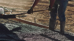 Construction worker wearing safety equipment spreading concrete - stock footage