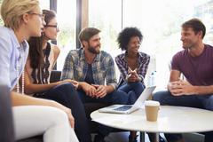 Businesspeople Having Informal Meeting In Modern Office - stock photo