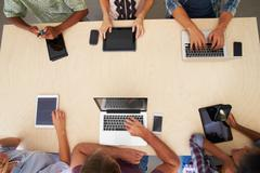 Overhead View Of Staff With Digital Devices In Meeting Stock Photos