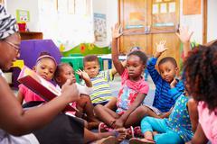 Class of preschool children raising hands to answer teacher Stock Photos