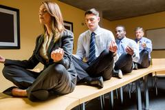 Business people doing yoga on table Stock Photos