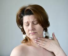 Adult woman with a sore throat on ight background Stock Photos