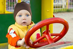 One year small boy at the car wheel - stock photo