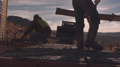 Construction workers backlit by the sun while spreading concrete - stock footage