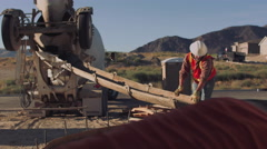 Worker with safety gear pouring concrete - stock footage