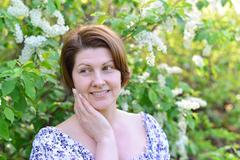 adult woman near blossoming bird cherry in the park - stock photo