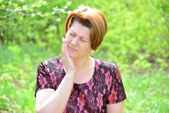 Stock Photo of woman with a toothache on the nature