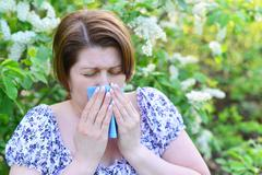 Adult female with allergic rhinitis about bird cherry blossoms Stock Photos