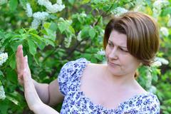 adult woman with allergic diseases removed from wild cherry blossoms - stock photo