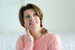 Portrait of positive woman in pink sweater - stock photo