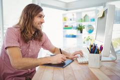 Hipster working on graphics tablet and computer - stock photo