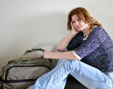 Sad woman sitting near the wall with suitcase because divorce - stock photo