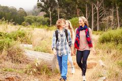 Mother and two kids walking on a forest trail Stock Photos