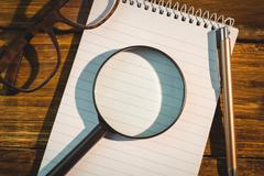 High angle view of magnifying glass with pen and notepad Stock Photos