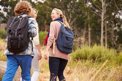 Mother and two kids walking on a forest trail, back view Stock Photos